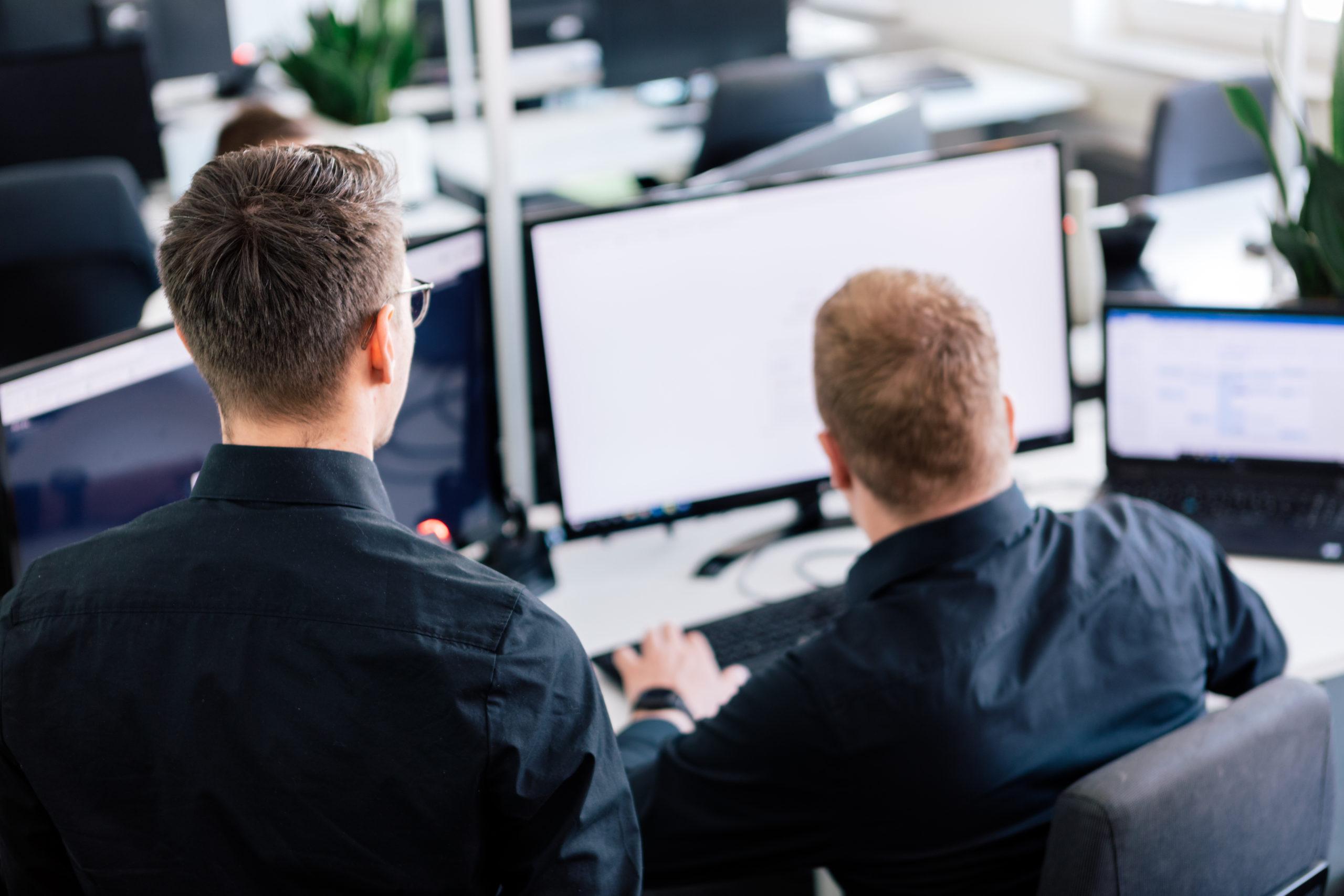 Hochwinkelaufnahme Zwei Geschäftsleute stehen vor einem Computer.